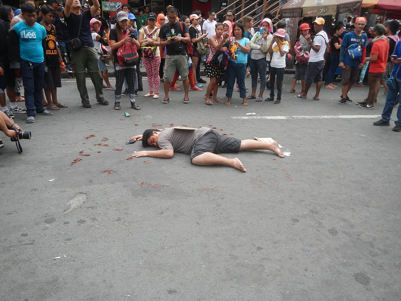 Demonstrator reenacts what the (alleged) extrajudicial killing looked like. Writing on the cardboard placed on the body was typically used in the crime allegedly related to drugs since Rodrigo Duterte was inaugurated as the president.