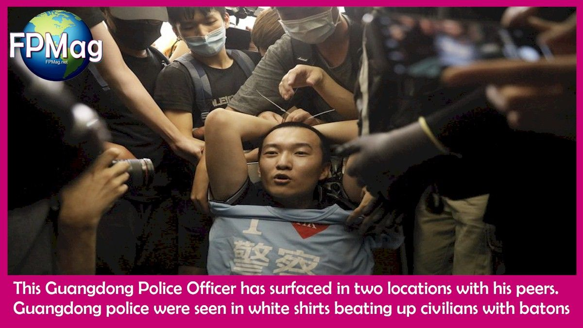 Guangdong Police officer says witnesses. This man is restrained on Tuesday by students. Photo Credit: Vincent Yu / AP