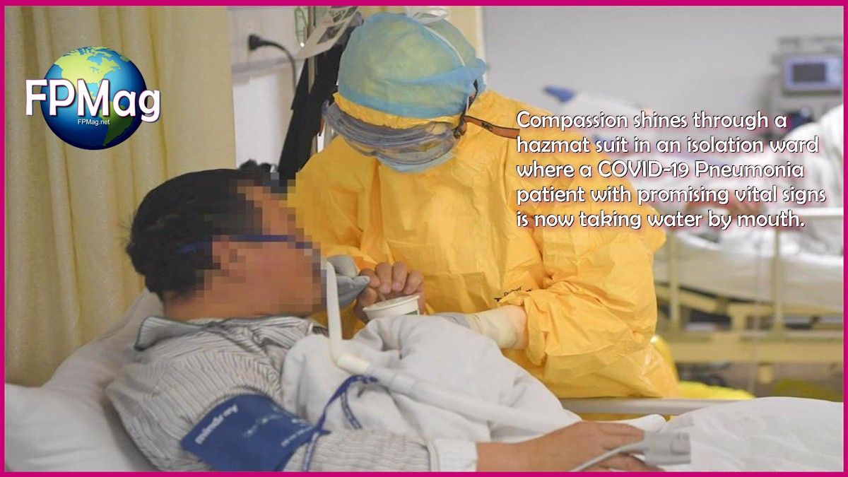 Compassion shines through a hazmat suit in an isolation ward where a COVID-19 Pneumonia patient with promising vital signs is now taking water by mouth.